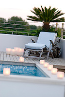White candles and a sun lounger decorate the swimming pool decking