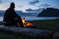 Man sits at evening campfire at Utakleiv beach, Lofoten Islands, Norway