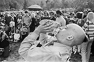 Hollywood, Los Angeles, CA. March 9th, 1969.<br /> A member of the religious organization, The International Society for Krishna Consciousness (ISKCON), known colloquially as the Hare  Krishna movement or Hare Krishnas, blowing a conch shell. <br /> The organization was founded in 1966 in New York City by A. C. Bhaktivedanta Swami Prabhupada.<br /> Griffith Park, Hollywood, Los Angeles, Californie. 9 mars 1969.<br /> Un membre des Krishna utilise une coquille de conche comme instrument traditionnel de musique.