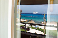 a cruise ship and a caribbean landscape is reflected in the Presidente Intercontinental hotel room window. Cozumel, Quintana Roo, Mexico