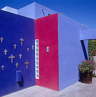 The vibrant colours of the exterior walls of this house in Mexico are intensified by the brilliant sunshine