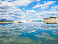 Billowy white clouds in a beautiful blue Montana sky are reflected on the water of Lake Koocanusa. The view is looking north in to British Columbia. The lovely snow capped peaks of the Canadian Rockies can be seen in the far distance.<br />