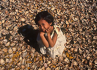 Girl amongs coconut chips production for coconut oil, Philippines