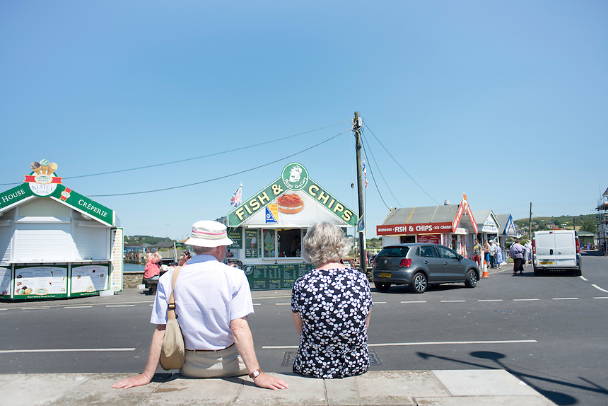 A couple sitting on the road infront of a fish and chips. Summer day at West Bay, Brid Port, Dorset, UK.