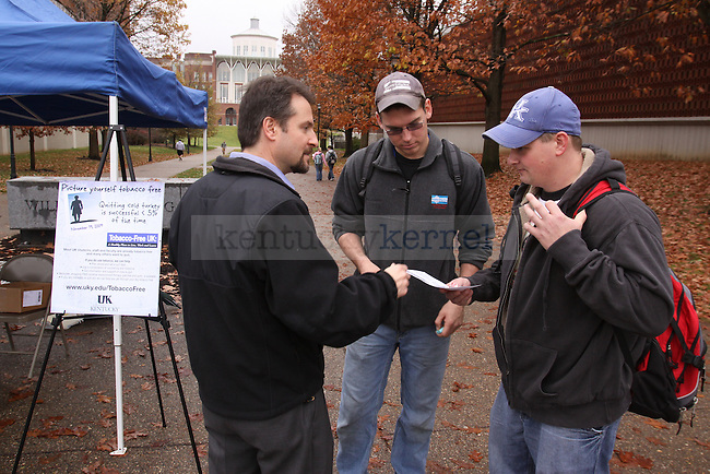 Felito Aldarondo, left, with the UK Counciling and Testing Center hands out candy and pamphlets that encourage quitting tobacco use to businees management junior Brad Meece, center, and engineering senior Craig See Wednesday afternoon. Photo by Scott Hannigan | Staff