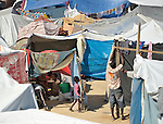 A homeless earthquake survivor constructs a temporary shelter in an already crowded soccer stadium in the Santa Teresa area of Petionville, Haiti. Hundreds of thousands of Haitians were left homeless by the January 12 quake.