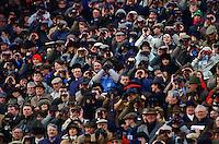 Racegoers watch racing at Cheltenham Races, Gloucestershire, United Kingdom