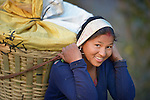 A woman carries a heavy load in Majhitar, a village in the Dhading District of Nepal.