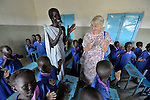 Students sing a song in a Catholic school in Malakal, Southern Sudan. Encouraging them is their teacher, Regina John Thabo (left, standing), who is studying to be a better teacher in a program sponsored by Solidarity with Southern Sudan, an international network of Catholic groups supporting Southern Sudan with educational personnel and prayer. Irish Sister Elizabeth Ryan, FCJ (right), supervises Thabo's progress. NOTE: In July 2011 Southern Sudan became the independent country of South Sudan.