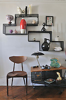 In the living room a set of retro shelves displays a collection of ceramics ranging from pieces by Picasso for Madoura to Marcel Wanders