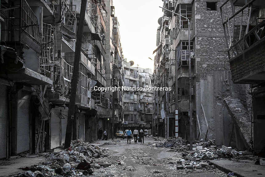 In this Saturday, Oct. 27, 2012 photo. Syrian residents walk on a street among the debris of buildings shattered by heavy shelling in Tarik Al-Bab neighborhood, southeast of Aleppo City. (AP Photo/Narciso Contreras).