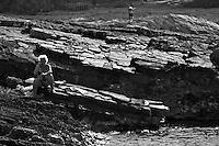 """Bagnanti a Porto Selvaggio. Nonostante non sia particolarmente agevole raggiungere la scogliera, negli ultimi anni il turismo di bagnanti è aumentato notevolmente - Reportage fotografico di Alessandro Caniglia, Alessandro De Matteis e Dario Luceri - Il Parco Naturale Regionale di Porto Selvaggio è situato lungo la costa ionica e ricade nel comune di Nardò (Lecce). Definito come """"area di notevole interesse pubblico"""" già nel 1939, è stato effettivamente istituito come Parco nel 2004. I suoi limiti sono compresi tra la baia di Frascone (a nord) e la Torre dell'Alto (a sud). Ha una estensione complessiva di circa 1000 ettari.Porto Selvaggio è una delle zone tra le più incontaminate del litorale Ionico, con un paesaggio caratterizzato da una pineta di ca. 300 ettari e da una macchia mediterranea ricca di acacee e ginestre..Lungo la costa sono presenti molte cavità carsiche, con varie insenature, grotte sommerse.Per gli amanti della natura il paesaggio è estremamente suggestivo in ogni stagione: molto silenzioso e rilassante in autunno, inverno e primavera, ricco di colori e festoso in estate, con il canto delle cicale che accompagna i visitatori lungo i sentieri e di tratti di scogliera che portano fino alla spiaggia. Il mare limpido e azzurro, con un fondale ricco di flora e fauna marina, è spesso meta di numerosi subacquei."""