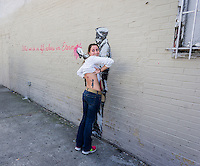 "A street art enthusiast shows off her Banksy inspired tattoo in the Woodside neighborhood of Queens in New York on Monday, October 14, 2013 in front of the fourteenth installment of Banksy's graffiti art, ""What we do in life echoes in Eternity"". The elusive street artist is creating works around the city each day during the month of October accompanied by a satirical recorded message which you can hear by calling the number 1-800-656-4271 followed by  # and the number of artwork.  (© Richard B. Levine)"