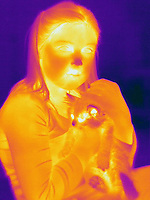 A Thermogram of a young girl and her cat.  The different colors represent different temperatures on the object. The lightest colors are the hottest temperatures, while the darker colors represent a cooler temperature.  Thermography uses special cameras that can detect light in the far-infrared range of the electromagnetic spectrum (900?14,000 nanometers or 0.9?14 µm) and creates an  image of the objects temperature..