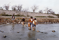 Del Rio, TX. January, 1983. <br /> The border patrol watches as many Mexicans made their daily journey accross the Rio Grande River into Del Rio, to work for the day, and return to Mexico the same evening.