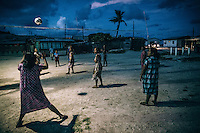 Women and children playing a game of volleyball in the evening on Ebeye's main square. Volleyball is very popular among local women and many of them come to the main square to play after they finish their daily household chores.