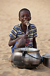 Cisse Al-Husseini, age 9, eats the remaining porridge from a pot in Timbuktu, a city in northern Mali which was seized by Islamist fighters in 2012 and then liberated by French and Malian soldiers in early 2013. The boy belongs to the Bella ethnic group, which has traditionally been exploited by Timbuktu's lighter-skinned groups.