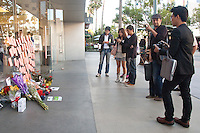 Mourners pay tribute to Apple co-founder Steve Jobs at a  makeshift memorial in front of the Apple store at the Third Street Promenade on Thursday, October 6, 2011.