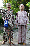 Two elderly women pose for a snapshot near the Citadel in the former imperial capital of Hue, Vietnam. April 22, 2013.