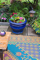 Tiny water garden with water lilies in blue pot container, outdoor colorful rug, patio, hanging lamp, shade garden plants, ferns, impatiens