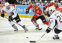 San Antonio Rampage's Eric Selleck, left, passes to teammate Mike Mottau, right, in front of Rockford IceHogs' Brad Winchester during the first period of an AHL hockey game, Saturday, Oct. 5, 2013, in San Antonio. (Darren Abate/M3D14.com)
