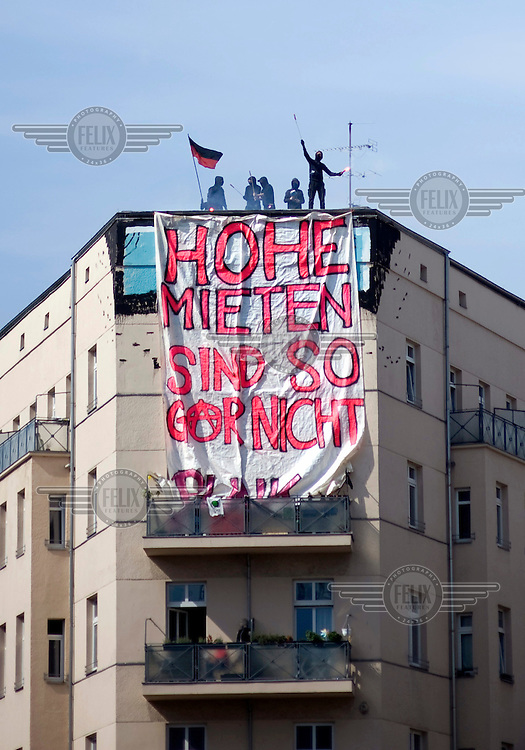 Poster reading Hohe Mieten Sind So Gar nicht Punk Rock (high rents are completely un-punk rock). Demonstration against the increase of rents and social displacement during a rally in Berlin Kreuzberg and Neukoelln. Berlin has been seeing an increase in protests opposing a steady process of gentrification which is rapidly forcing poorer residents out of the city centre and tearing apart the city's social fabric.