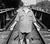 Michael Kelly, standing on the railroad tracks running over Erwin Rd., in Durham, August 1, 2008. ..Photo By Jeyhoun Allebaugh