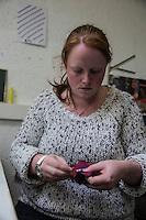 Artigiani al lavoro producono capi di abbigliamento a partire dal tweed donna che cuce