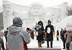 A couple has its photo taken in front of a sculpture of well-known anime character Chibi Maruko-chan and her friends during the Sapporo Snow Festival in Sapporo City, northern Japan on 5 Feb 2010.
