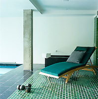 A contemporary teak sunbed on the green-tiled floor at one end of this indoor swimming pool