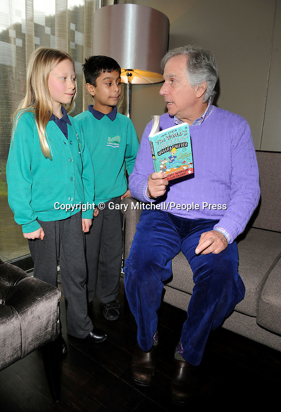 Milton Keynes, UK -  Actor and dyslexic author Henry Winkler - aka 'The Fonz' - meets children from local schools in Milton Keynes. .Henry is touring schools and theatres with Nicky Cox, editor of children's newspaper First News as part of the '2013 First News My Way' campaign, in partnership with Charity, Achievement for All 3As. .Pictured - Henry Winkler with Hannah Bartrum- Carter and Yash Tailor, Milton Keynes Theatre, Bucks, UK - 8th March 2013..Photo by Gary Mitchell