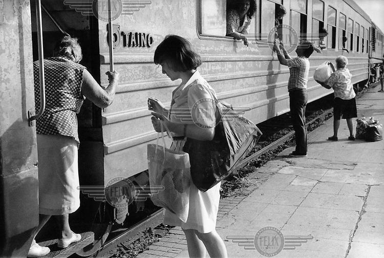 People board a train in Havana.