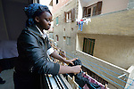 Rebecca Jacob retrieves laundry from drying outside their fifth floor apartment in Cairo, Egypt. The family fled violence in South Sudan, and today Rebecca and her siblings attend classes provided by St. Andrew's Refugee Services, which is supported by Church World Service.