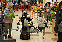 """All of these robotics folks developing robots for elderly talk about studies showing that more and more elderly are isolated and have no one to relate to... In 2009 it was 19 percent of the elderly population of Japan.  They have a word for it:  """"Kodokushi"""" or """"lonely death."""".The robotics folks at Keihanna Science City.http://www.kri-p.jp/english/history.html.http://web-japan.org/atlas/technology/tec07.html.cite these studies and are developing robots to help with shopping and other chores.  But mostly they are developing a companion to combat kodokushi.  The elderly Japanese person fills out a shopping list on their iPhone at their home and it is sent to the robot at the grocery store... when they walk into the store the robot recognizes them from the geolocation info in their iPhone and accompanies them on their shopping tasks, carrying the basket, reminding them of the items on their list and giving them information about the best freshest products that have come into the store on that day.  The eyes of the robot follow wherever the iPhone is to give the elderly the impression they have a friend.  The elderly woman shopping in this example is Nabeshima Akiko.  This grocery store is a functioning grocery store in the science city and is set up for demos of what this technology CAN do... but it is not functional yet.  They hope it will be in five years."""