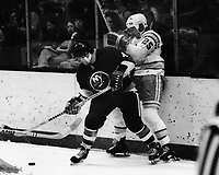 Seals vs New York Islanders 1975, Jean Potvin and Seals Al MacAdam mix it up on the boards. (photo 1975 by Ron Riesterer)