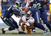 Antonio Brown #84 of the Pittsburgh Steelers is tackled between defenders after catching a pass in the second half against the Seattle Seahawks during the game at CenturyLink Field on November 29, 2015 in Seattle, Washington. (Photo by Jared Wickerham/DKPittsburghSports)