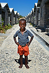 """Woodmay Pajeotle, 3, stands on a path amid houses in a model resettlement village constructed by the Lutheran World Federation in Gressier, Haiti. The settlement houses 150 families who were left homeless by the 2010 earthquake, and represents an intentional effort to """"build back better,"""" creating a sustainable and democratic community. This boy and his mother are among the residents."""