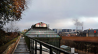 Plant History Glasshouse (formerly Australian Glasshouse), 1830s, Rohault de Fleury, Jardin des Plantes, Museum National d'Histoire Naturelle, Paris, France. View from the side of the glass and iron roof, seen from the incubator roof, with the main avenue of the Jardin des plantes to the right, and the Paris skyline beyond.