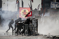 In this Tusday, Jun. 11, 2013 photo, protesters take cover from tear gas canisters shot by the anti-riot police duriing clashes at the streets of Taksim Square in Istanbul,Turkey. (Photo/Narciso Contreras).