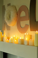 A row of lit candles on a mantelpiece beneath a Noel sign featuring a wreath made of white feathers