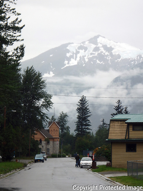 snow capped mountain at he end of a street in the Alaskan town of Skagway on a rainy day