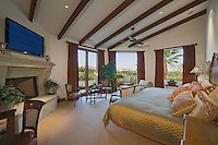 Master bedroom with very large bed, fireplace, beamed ceilings in Mediterranean style