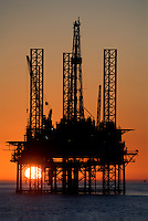Stock photo of a jackup oil and gas drilling rig silhouette at sunset in the Gulf of Mexico.