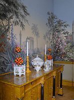 A Biedermeier sideboard in the dining room with walls covered in French Zuber panoramic wallpaper