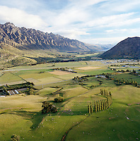 View across farmland towards Southern Alps from helicopter, Queenstown, Southern Alps, South Island, New Zealand.