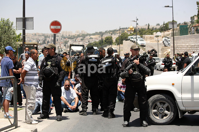 Israeli riot police stand guard as Palestinian muslim worshipers attend the Friday prayers in the East Jerusalem neighbourhood of Ras al-Amud after being refused entry into the Al-Aqsa compound in Jerusalem, 30 May 2014. The Israeli police restricted the entrance to the Al-Aqsa mosque and permitted only men over the age of 45 due to intelligence reports of planned disturbances by Palestinians on al-Aqsa compound. Photo by Saeed Qaq