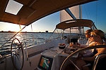 A couple dines as they watch the sunset from a beneteau 49 sailboat yacht in charleston south carolina Sailing
