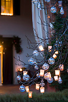 Close up of tealights and glass baubles hanging from the bare branches of a tree in the garden