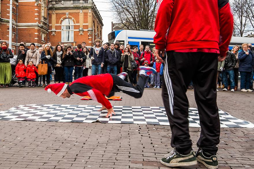 Nederland, Amsterdam, 13 dec 2014<br /> Breakdance show van russische jongens op het Leidseplein, Amsterdam.  Toeristen staan er in een grote kring om heen. Het is een moderne vorm van bedelen voor wat vrijwillige bijdragen in de hoed.<br /> <br /> Foto: (c) Michiel Wijnbergh