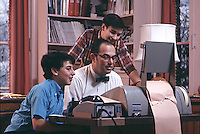 Father at work on his home computer with two sons, 1970. The computer system, known as 'time-sharing,' consisted of a teletype terminal connected to a big central unit via telephone. Photo by John G. Zimmerman.